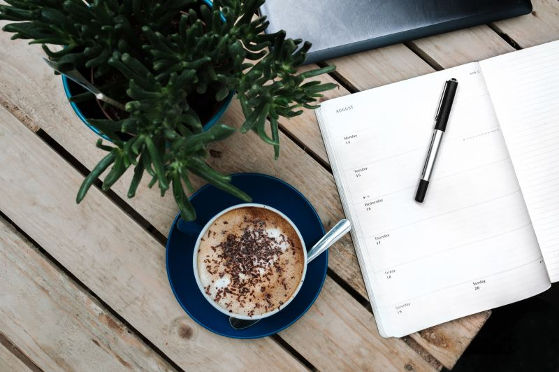 planner with hot chocolate cup and pen